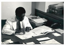 Harold Amos at his desk